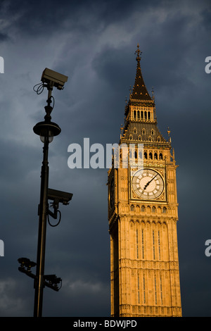 Big Ben and security cameras, in stormy and cloudy sky and weather, London, England, at sunset. Focus on security - Stock Photo