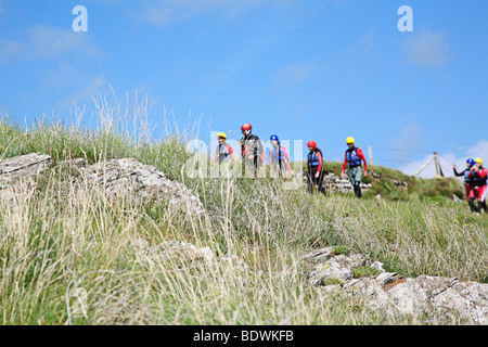 Coasteerers walking along the Pembrokeshire coastal path. - Stock Photo