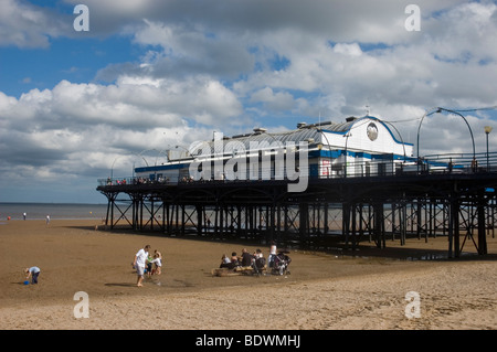 People on the beach near Cleethorpes Pier at low tide - Stock Photo