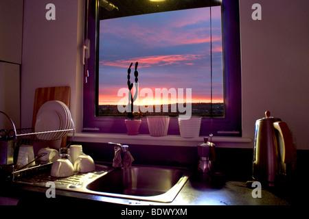 HDR sunset seen through a kitchen window - Stock Photo