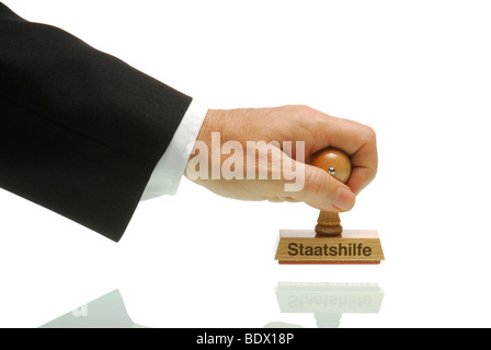 Business man holding a stamp with the lettering Staatshilfe, German for government support - Stock Photo