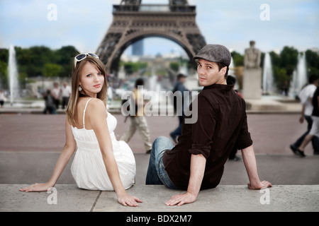 Young couple sitting in front of the Eiffel Tower, direct view, Paris, France, Europe - Stock Photo