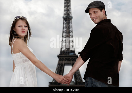 Young couple, hand in hand in front of the Eiffel Tower, Paris, France, Europe - Stock Photo