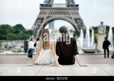 Young couple sitting in front of the Eiffel Tower, Paris, France, Europe - Stock Photo