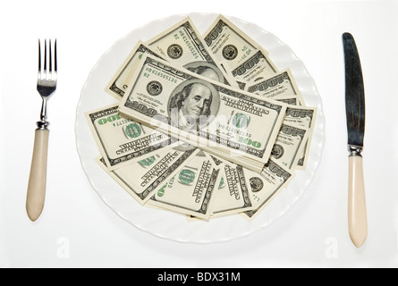 Money on plate with fork, knife - Stock Photo