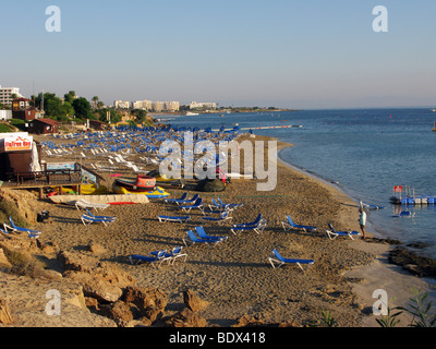 Empty sunbeds in early morning on the beach at Fig Tree Bay, at the village of Protaras, Cyprus. - Stock Photo