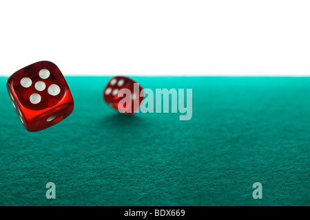 Two red dices rolling over a green felt against a white background. - Stock Photo
