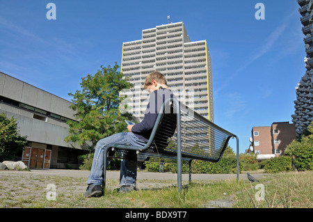 Boy, 9, playing with his Nintendo in front of a high-rise apartment building, satellite town of Chorweiler in Cologne, - Stock Photo