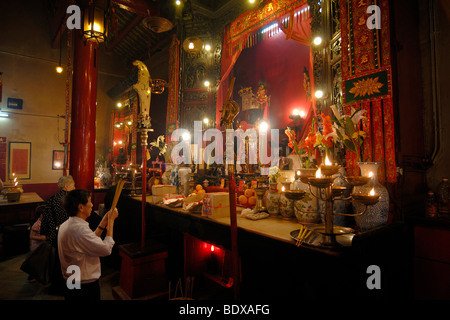 Man and woman praying with incense sticks, smoke sacrifice, in front of a Chinese Buddhist altar with burning candles and offer