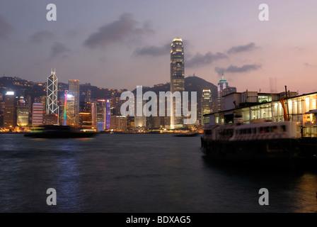 Star Ferry at the illuminated Star Ferry Kowloon pier, overlooking the illuminated nightly skyline of Hong Kong - Stock Photo