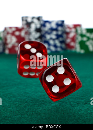 Two red dices rolling over a green felt. Out of focus stack of colorful chips on the background. - Stock Photo
