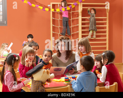 kindergarten teacher playing games with children - Stock Photo