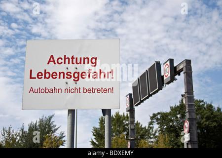 Warning sign on a highway 'Achtung Lebensgefahr! Autobahn nicht betreten!' 'Attention, mortal danger! Do not enter - Stock Photo
