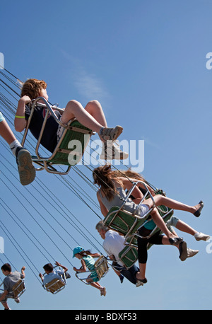 People on a chairoplane at a fun fair - Stock Photo