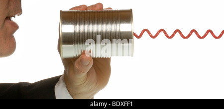 Business man with tin and telephone cable, a symbolic image for communications - Stock Photo