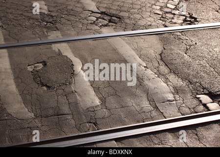 Tram tracks in cobbled damaged street - Stock Photo