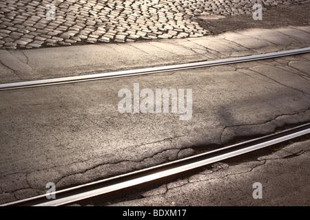 Tram tracks in cobbled damaged street - Stock Photo