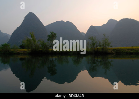 Karst cliffs and rice fields at harvest time are reflected in the Yulong River in the karst landscape in Yangshuo, - Stock Photo