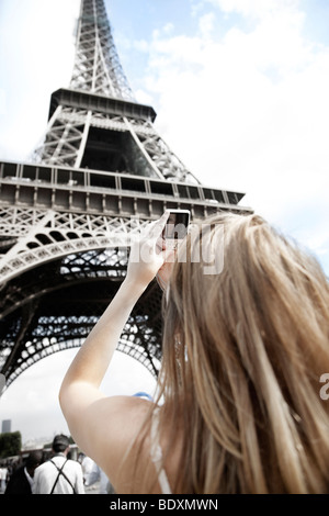 Young woman taking a picture on the Eiffel Tower, Paris, France, Europe - Stock Photo