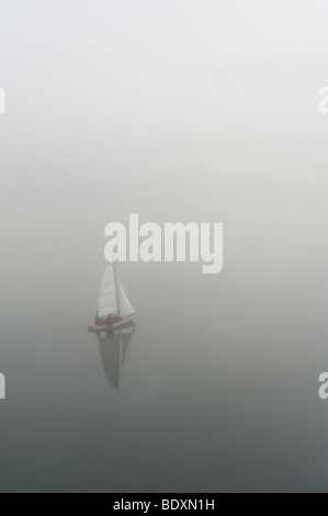 Sailboat in the fog on a lake - Stock Photo