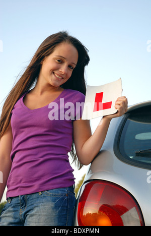 Happy young teenage girl learning to drive holding L plate - Stock Photo