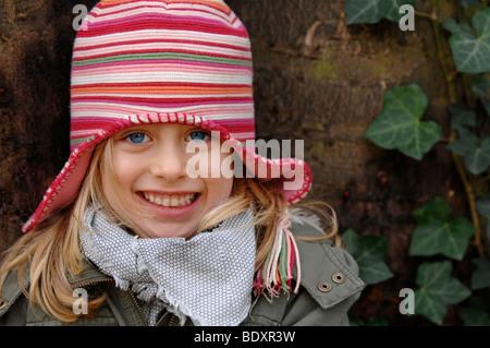 Six-year-old girl wearing a woollen hat in winter, portrait - Stock Photo