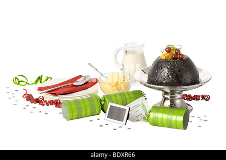 Christmas pudding with brandy butter, cream and christmas crackers. - Stock Photo