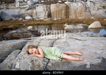 Toddler taking a nap outside. - Stock Photo