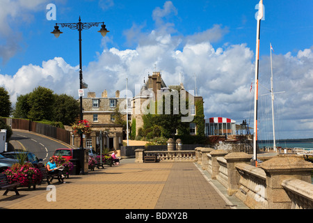 View of the Parade and the Royal Yacht Squadron, people sit on the benches in the sun reading, West Cowes, Isle - Stock Photo