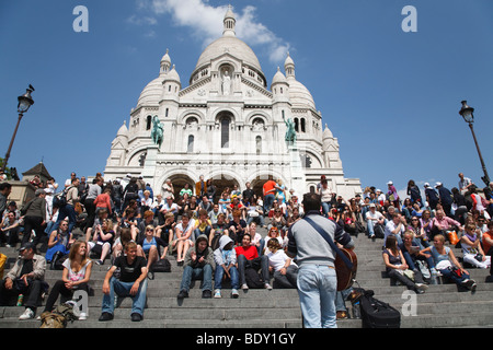 Tourists listen to a street entertainer on the steps before Sacre Coeur, Paris, France - Stock Photo