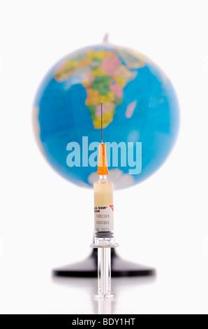 Syringe and globe, symbolic of vaccination against swine flu, pandemic - Stock Photo