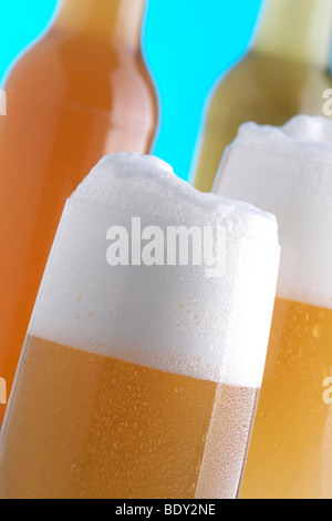 Full glasses of beer in front of beer bottles - Stock Photo