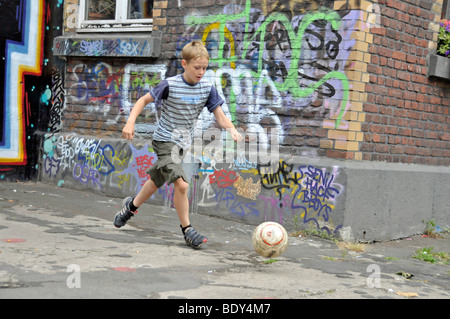 Nine-year-old boy playing with his football in front of a graffiti wall, kickabout area in Cologne, North Rhine - Stock Photo