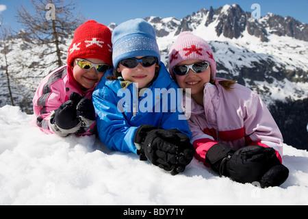 Three kids lying in the snow. - Stock Photo