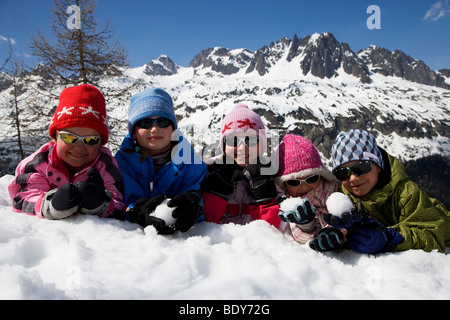 5 kids lying in the snow. - Stock Photo
