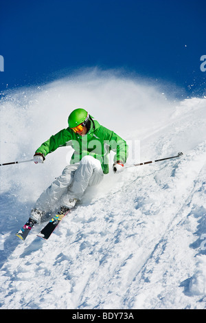 Man in green carving off piste. - Stock Photo