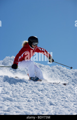 Girl in red carving off piste. - Stock Photo