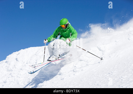 Man in green skiing off piste. - Stock Photo