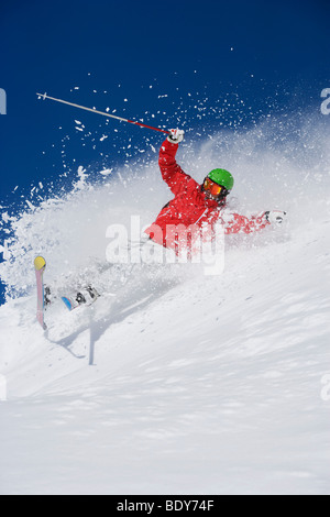 Man in red falling mid carve off-piste. - Stock Photo