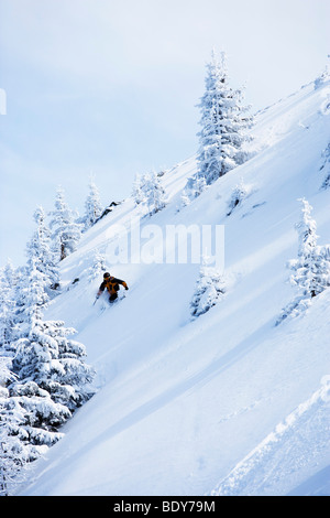 Man in black & orange outfit off-piste. - Stock Photo