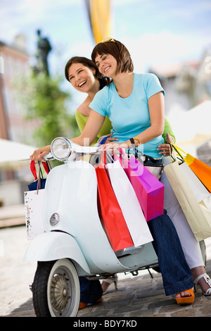 girlfriends with motor scooter laughing - Stock Photo