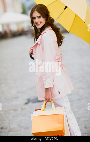 girl goes shopping in the rain - Stock Photo