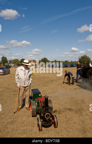 A man inspecting a scale model traction engine at a country show in Essex. - Stock Photo