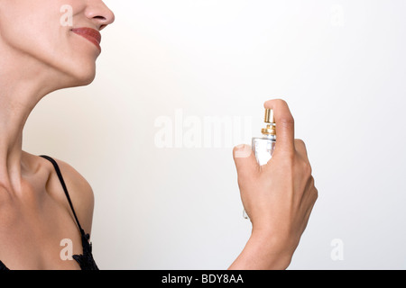 woman putting some perfume on her - Stock Photo