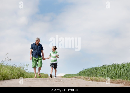 Father and son walking down a road - Stock Photo