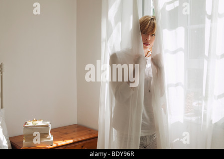 Woman standing behind curtain - Stock Photo