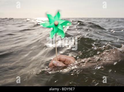 Arm holding windmill towards sea - Stock Photo