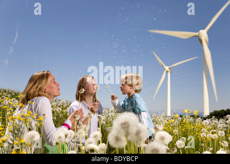 Girl and boy and mother at wind turbines - Stock Photo