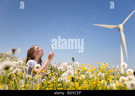 Girl blowing dandelion at wind turbine - Stock Photo