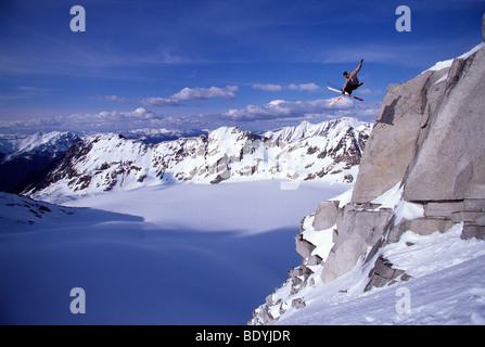 Skier jumping off a cliff - Stock Photo